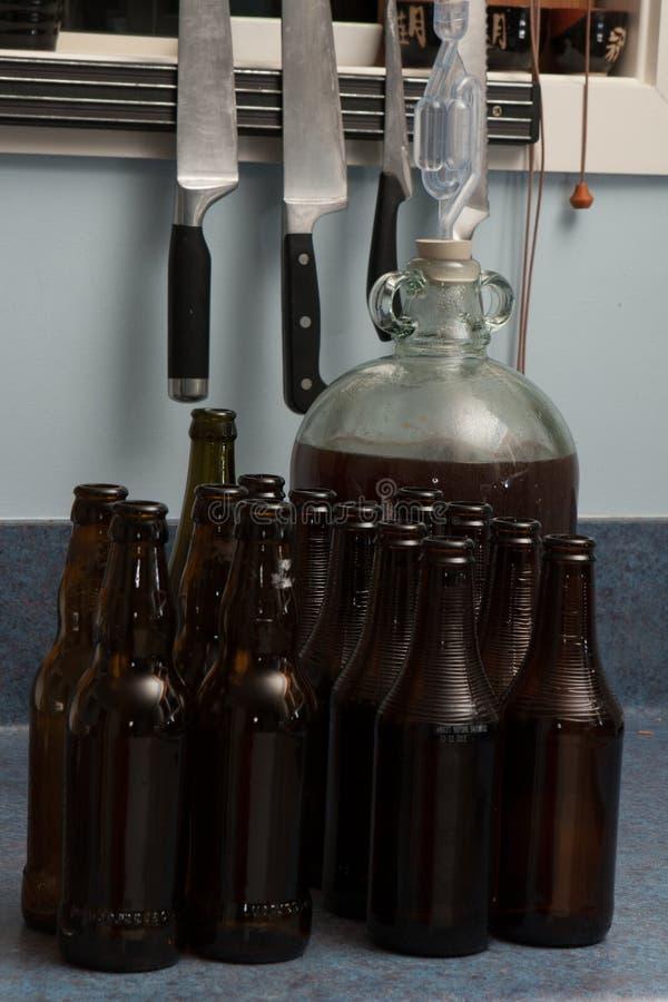 篮装的细类颈大坛fulled与气密室和黑褐色瓶的被发酵的啤酒 免版税库存照片