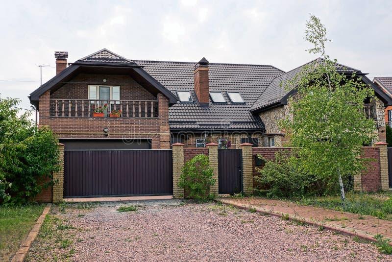 篱芭和金属棕色门长满与在一个私有房子前面的绿色植物 库存图片