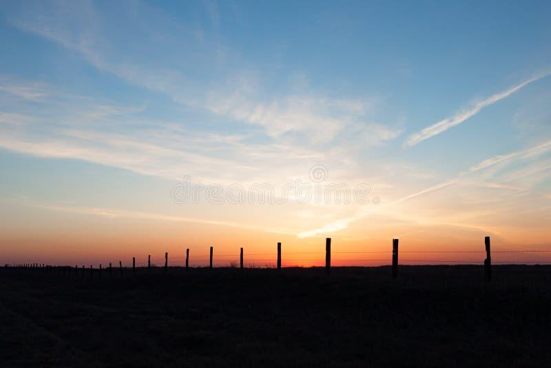 篱芭岗位线反对金黄日落的 库存照片