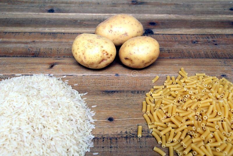 米、土豆和通心面面团在一张木桌上 提供能量,但是的三共同的碳水化合物可能导致肥胖病 免版税库存图片