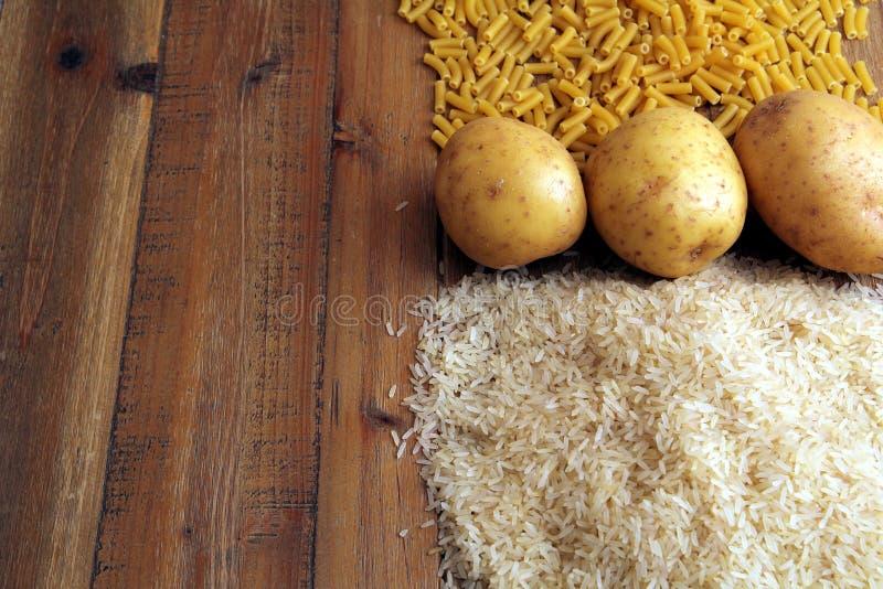 米、土豆和通心面面团在一张木桌上 提供能量,但是的三共同的碳水化合物可能导致肥胖病 免版税库存照片