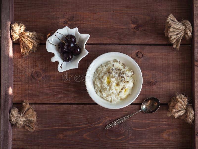 米与向日葵种子和樱桃莓果的牛奶粥白色早餐在一个木盘子的白色薄酥饼,匙子 库存照片