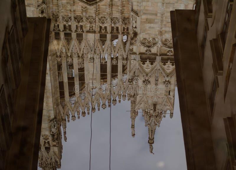 米兰中央寺院屋顶在水坑反射 免版税图库摄影