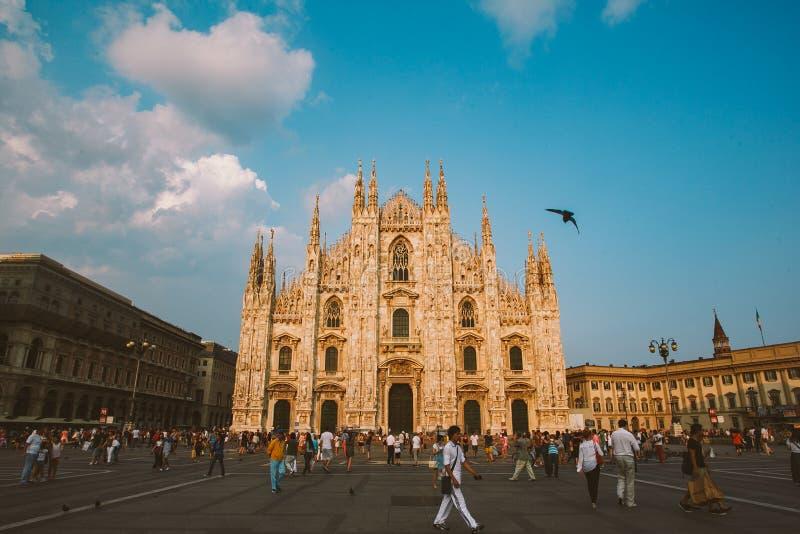米兰,意大利2013年7月13日:广场中央寺院,一许多人给在城市前面,二重奏的主要标志的正方形赋予生命 免版税库存照片