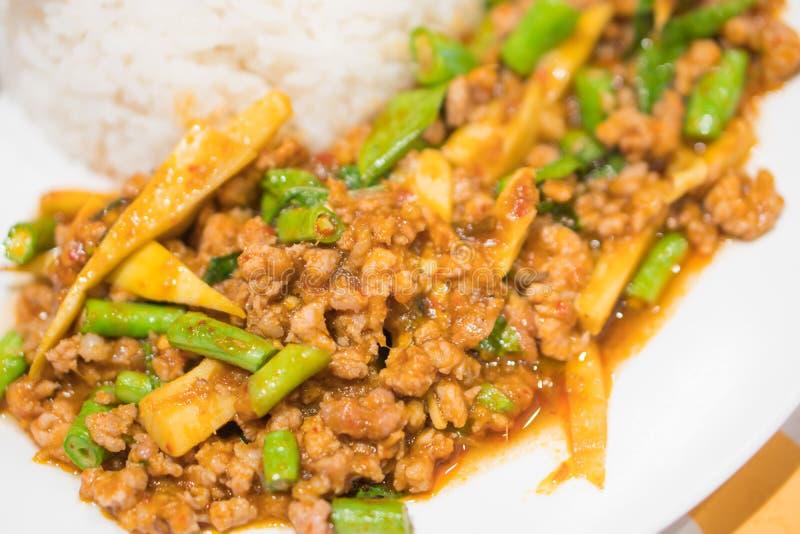 米冠上用混乱油煎的剁碎的猪肉和蓬蒿用煎蛋 免版税库存照片