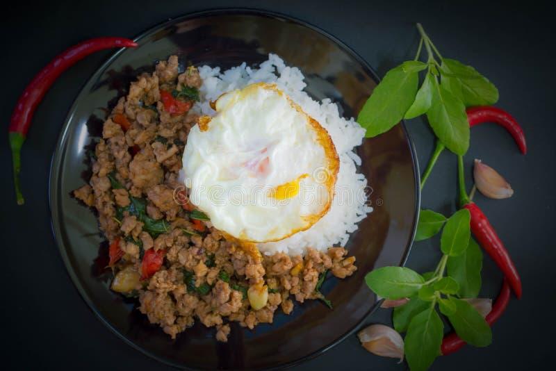 米冠上用混乱油煎的剁碎的猪肉和蓬蒿用煎蛋 免版税库存图片