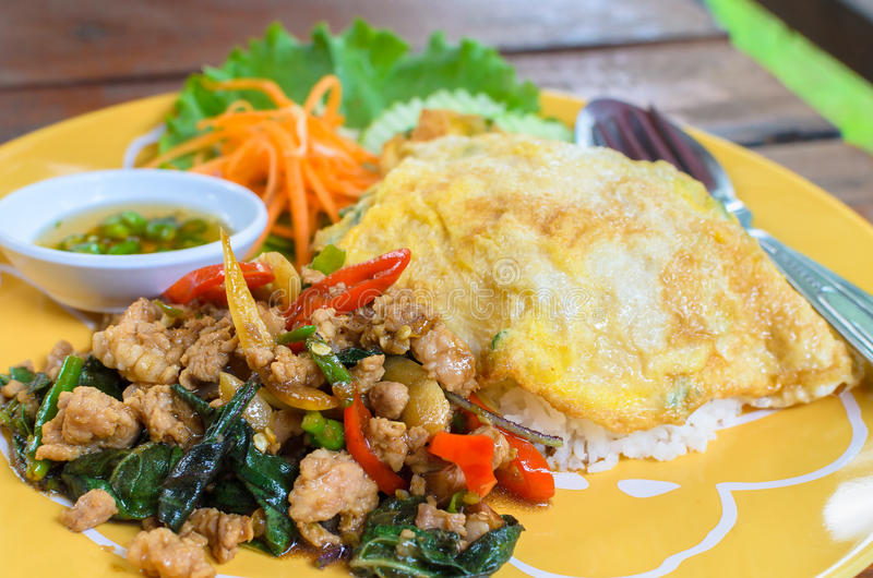 米冠上用混乱油煎的猪肉、蓬蒿叶子和辣椒 免版税库存图片