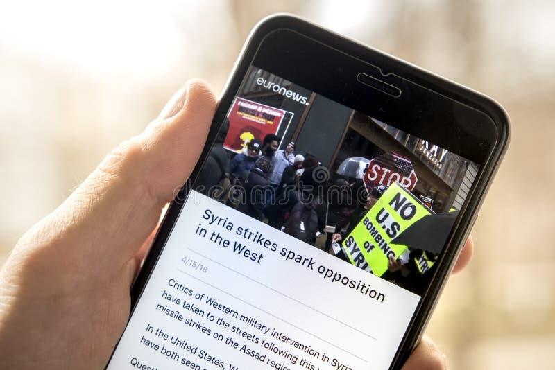 米斯克,白俄罗斯- 2018年4月14日:文章关于罢工在现代智能手机屏幕上的叙利亚在euronews在手中开辟app 免版税图库摄影