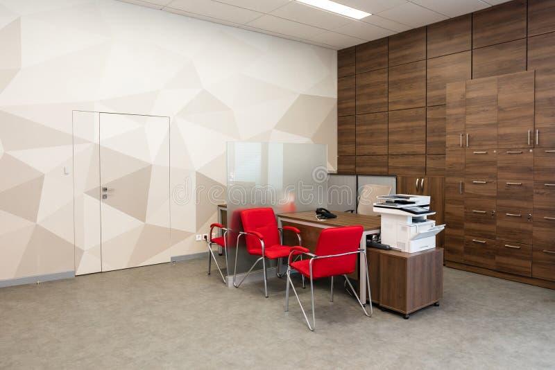 米斯克,白俄罗斯- 2019年5月23日:现代办公室的角落有白色和木墙壁的,灰色地板,与红色的露天场所区域 免版税库存图片