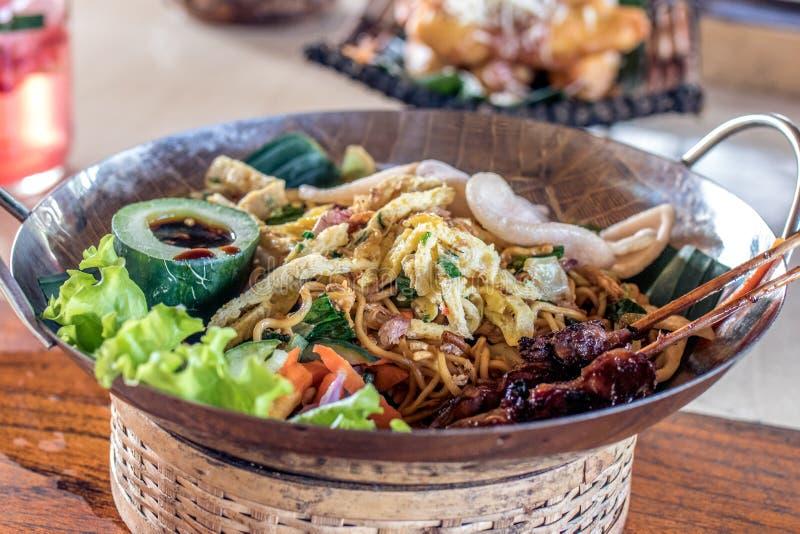 米氏goreng, mi goreng,印度尼西亚语油煎了与美丽的装饰的面条在一张木桌上 巴厘岛 免版税库存照片