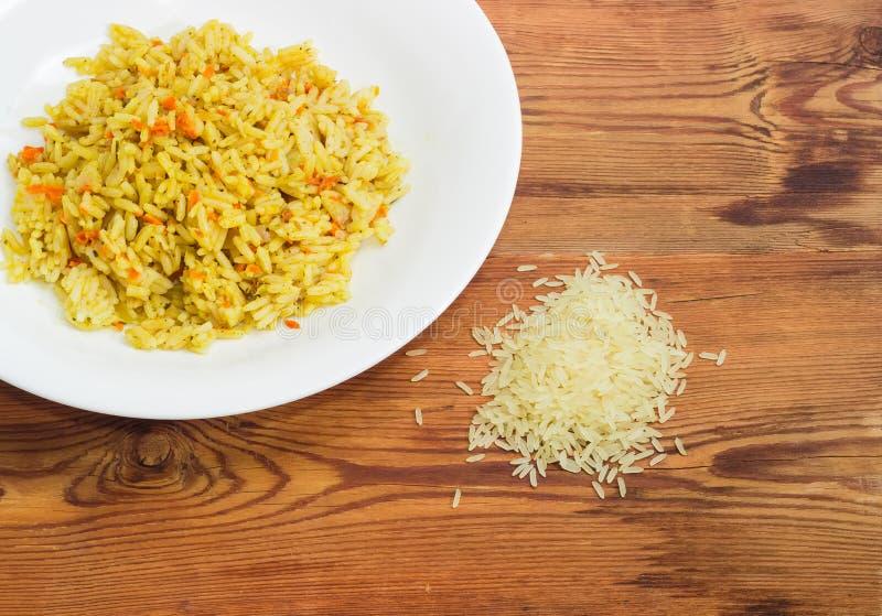 米烹调了用红萝卜和香料和在未煮过的米旁边 免版税库存照片