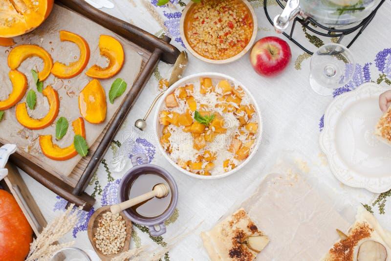 米用南瓜和蜂蜜在桌和其他秋天食物,饼上用梨 可口家庭晚餐在庭院里 看法从 库存照片
