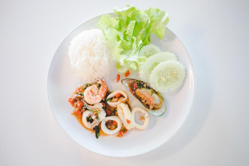 米用混乱油煎的海鲜和蓬蒿与荷包蛋用莴苣和黄瓜盘装饰在泰国餐馆 免版税图库摄影