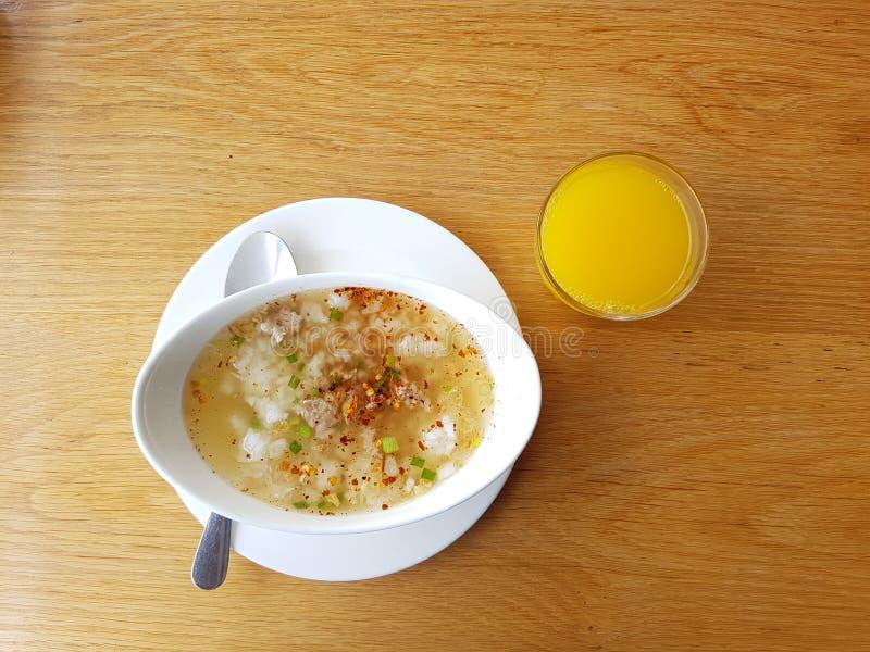米用猪肉煮沸了与橙汁过去和饮用水的早餐在woodeb桌上 & x28;亚洲传统食物 免版税库存照片