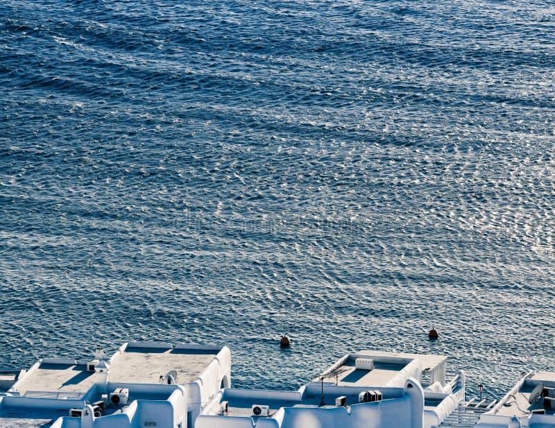 米科诺斯岛镇港口的全景有著名风车的从上述小山在一个晴朗的夏日,米科诺斯岛,基克拉泽斯, 库存图片