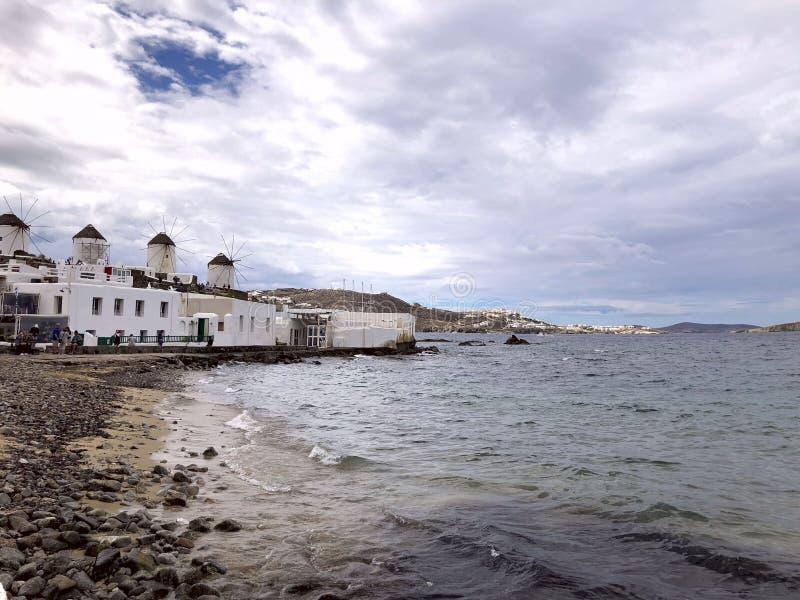 米科诺斯岛,希腊海岛的海岸  在左边是海湾的白色大厦以多云sk为背景 免版税图库摄影