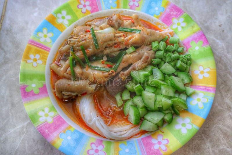 米粉特写镜头加水、红色咖喱、鸡腿、新鲜的绿色菜、泰国食物或者中国面条 库存照片
