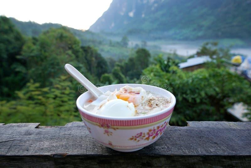 米粥用被煮半熟的鸡蛋、剁碎的猪肉和胡椒在木桌上,米稀饭或者鞠躬在森林里 免版税库存图片