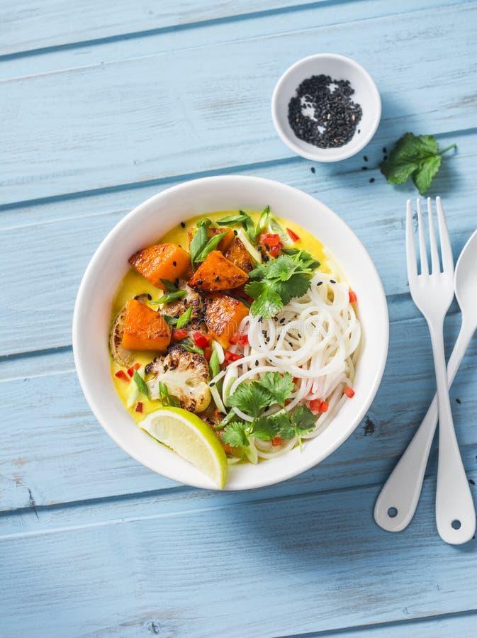 米线用烘烤南瓜、花椰菜和咖喱汁在蓝色木背景 免版税库存照片