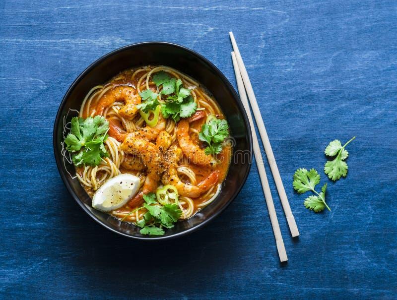 米线用虾在蓝色背景的咖喱汁 免版税库存照片
