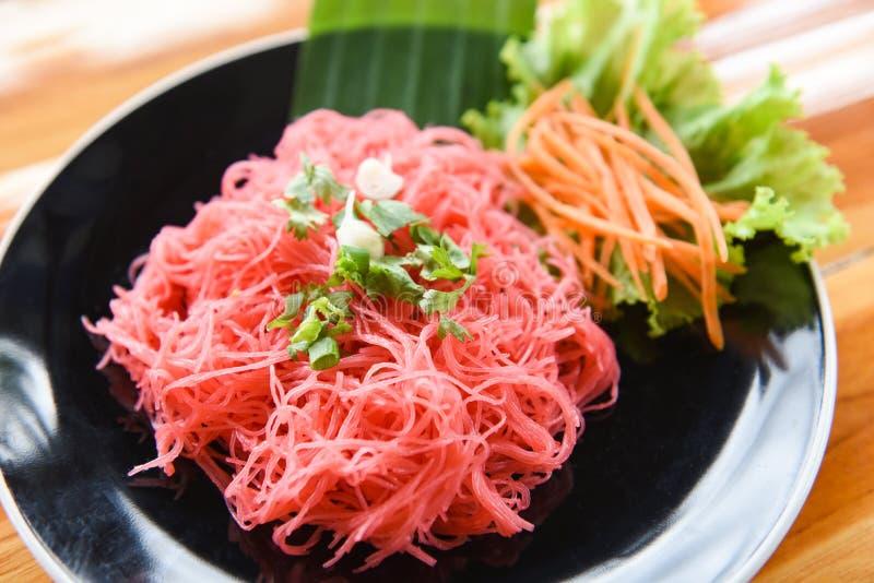 米细面条桃红色油煎和菜/混乱炒米米线用在木桌泰国亚洲人的板材供食的红色调味汁 免版税图库摄影