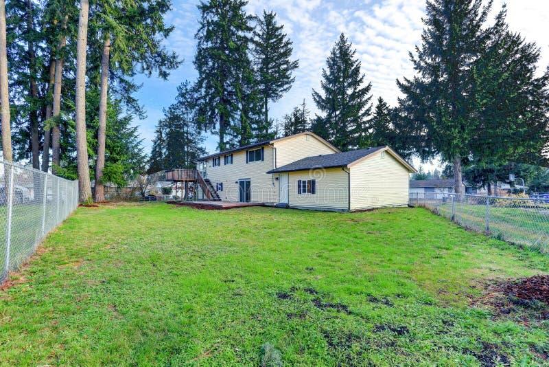 米黄二层的家外部与快门 免版税库存照片