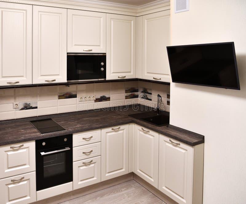 米黄厨房和电视的片段在墙壁上 免版税库存图片