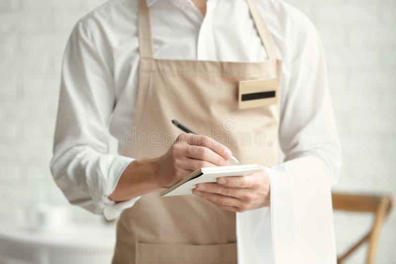 米黄围裙的侍者写下命令的在咖啡馆 库存图片