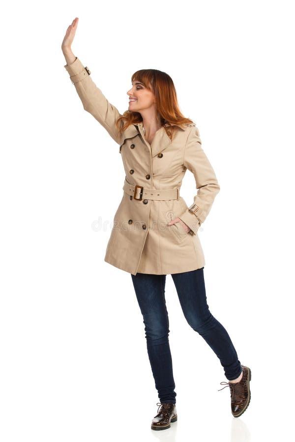 米黄外套、牛仔裤和布朗鞋子的年轻女人看和挥动手 免版税图库摄影