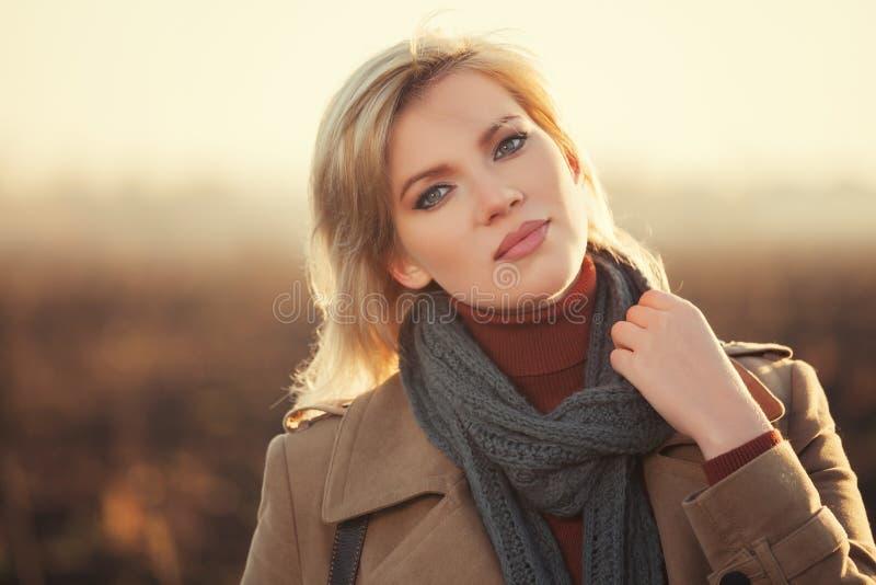 米黄外套和灰色围巾走的年轻时尚妇女室外 免版税库存图片