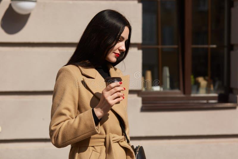 米黄外套的年轻美女有提包的走在街道上的isdolated在咖啡馆背景,有直接长的黑发, 库存图片