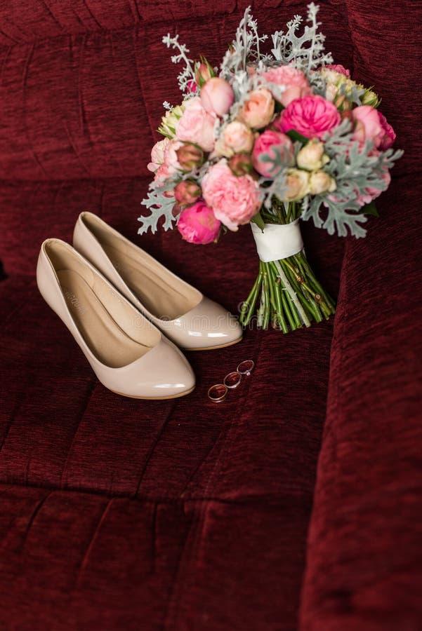 米黄新娘鞋子和说谎在一把红色扶手椅子的婚戒 与紫色和桃红色玫瑰的婚礼花束在焦点外面 免版税库存照片