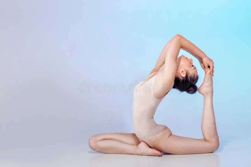 米黄泳装的亭亭玉立的体操运动员 免版税图库摄影