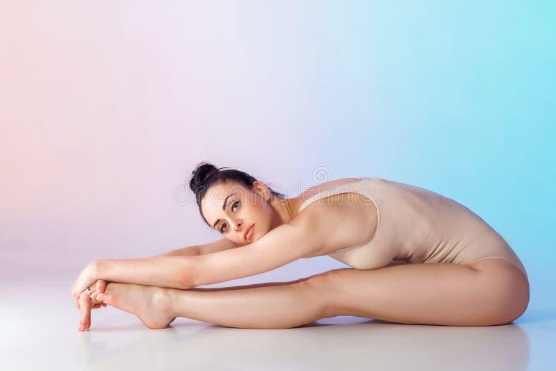 米黄泳装的亭亭玉立的体操运动员 免版税库存照片