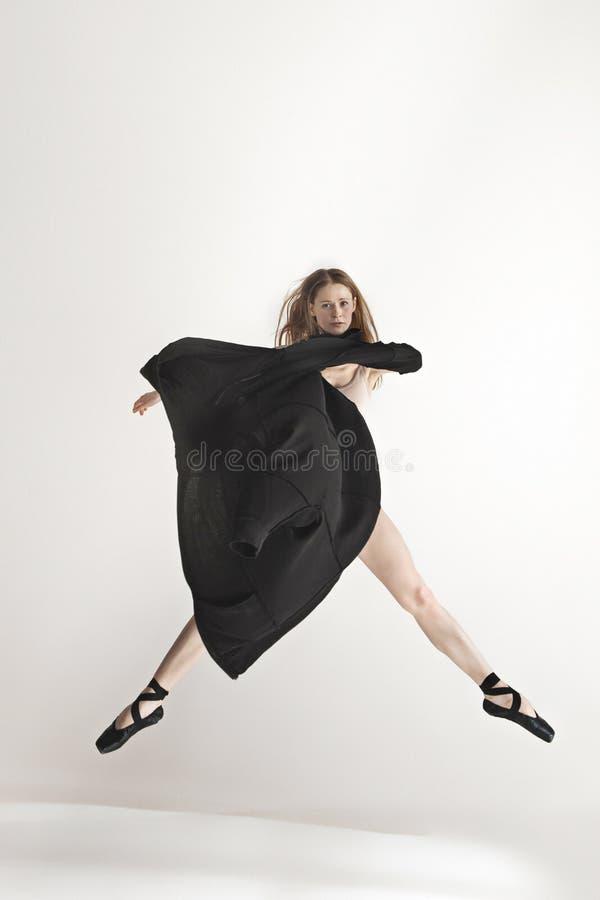 米黄泳装跳舞的年轻美丽的舞蹈家在灰色背景 免版税库存照片