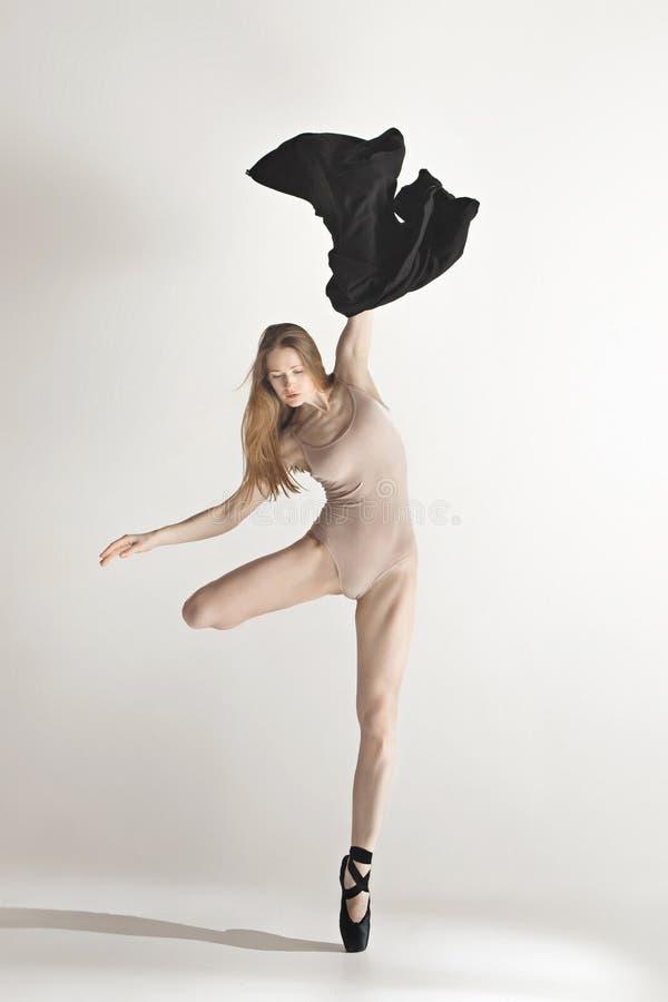 米黄泳装跳舞的年轻美丽的舞蹈家在灰色背景 免版税库存图片
