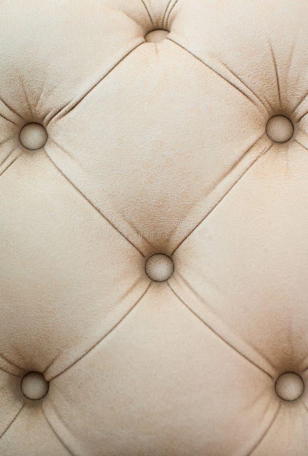 米黄皮革室内装饰品背景,从沙发的片段 免版税库存图片