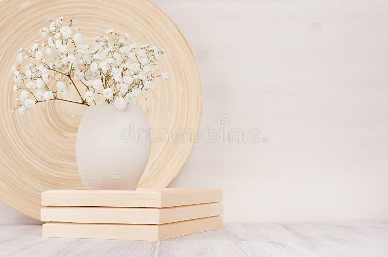 米黄竹盘软的家庭装饰和在陶瓷花瓶的白色小花在白色木背景 内部 免版税库存图片