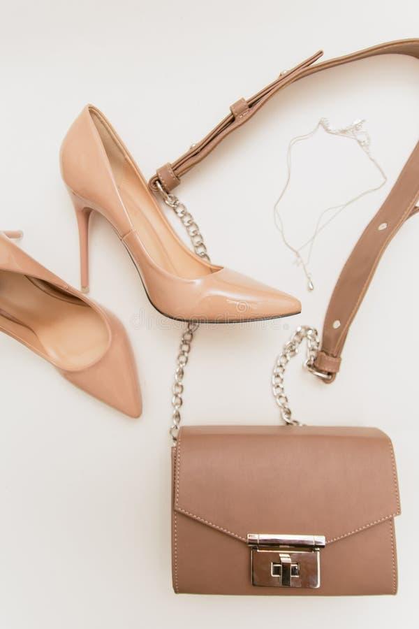 米黄鞋子和袋子在轻的背景 免版税图库摄影