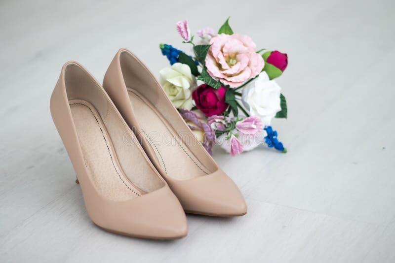 米黄鞋子 婚姻的鞋子 在脚跟的新娘鞋子 新娘` s费 婚礼装饰 图库摄影