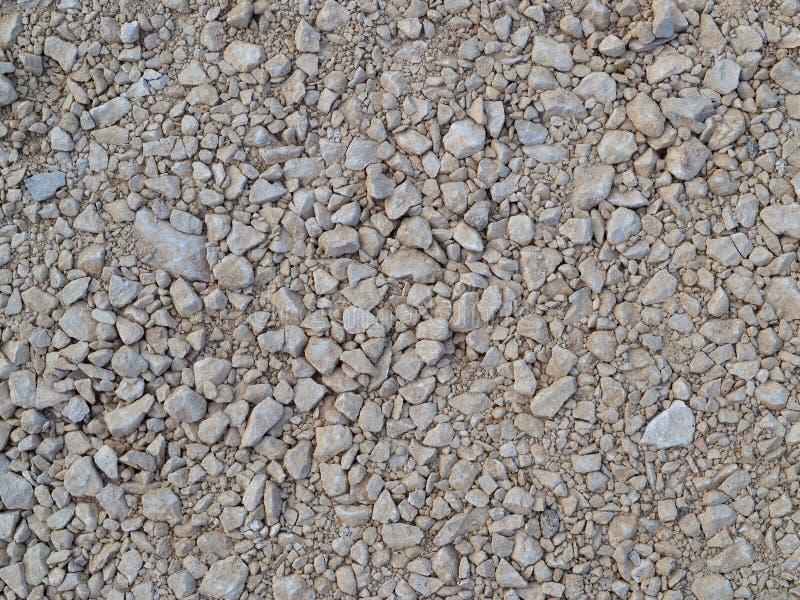 米黄颜色变紧密的瓦砾纹理在道路施工工作站点的  免版税库存照片