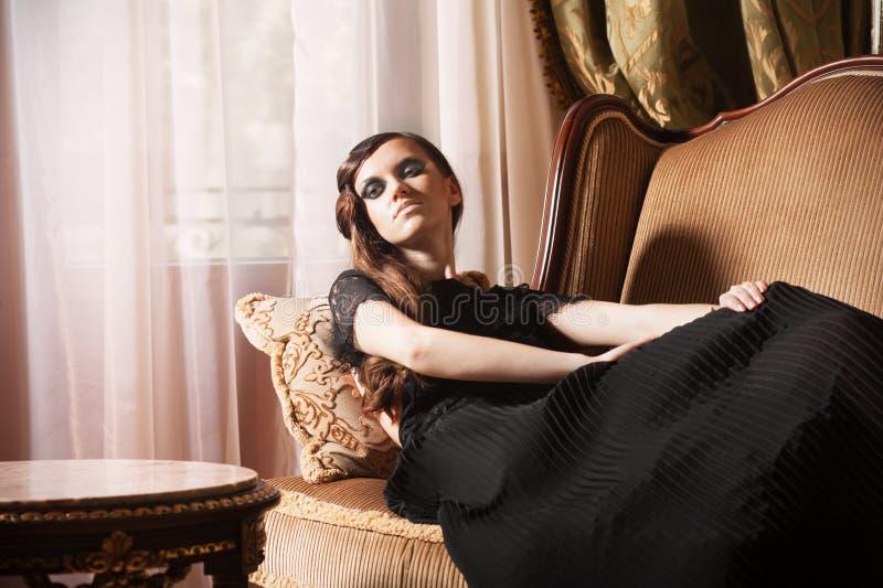 米黄魅力沙发妇女年轻人 库存照片