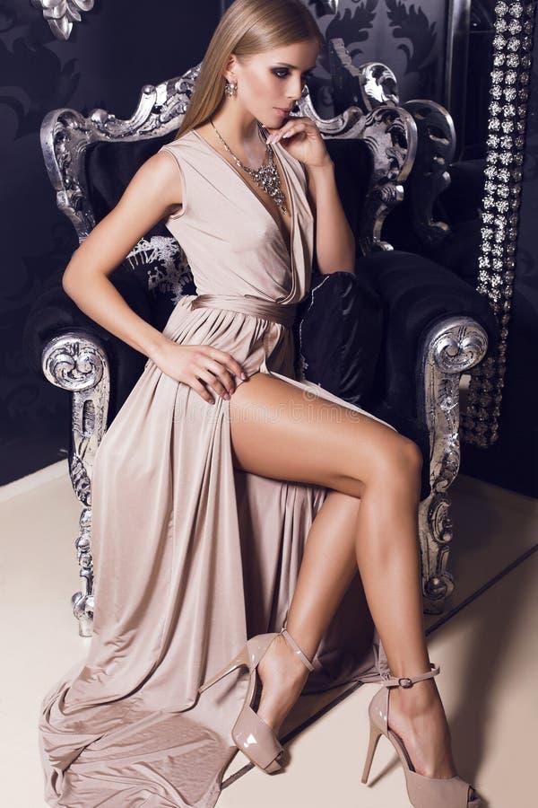 米黄丝绸礼服的性感的妇女坐黑扶手椅子 库存图片