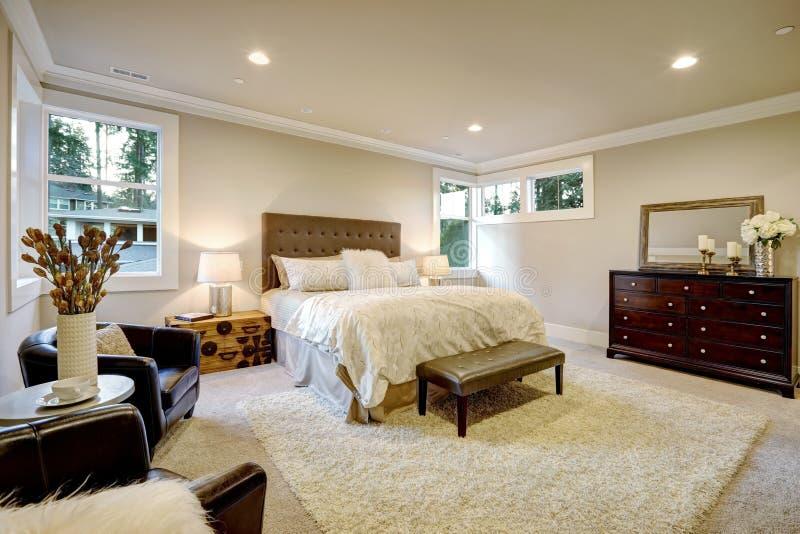 米黄和棕色主卧室吹嘘装缨球大号床 库存图片