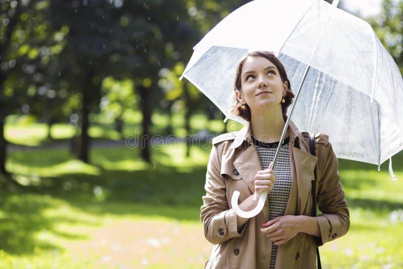 米黄外套和下毛毛雨的雨下落的妇女 免版税库存图片