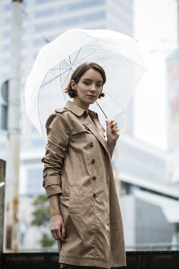 米黄外套的妇女在有伞的台阶 免版税库存照片