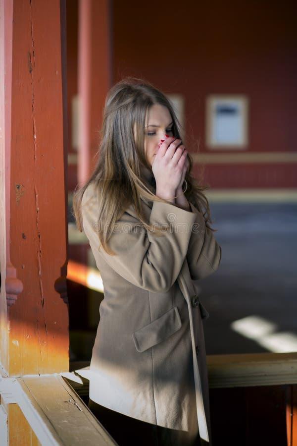 米黄外套的妇女感觉温暖的呼吸 免版税库存照片