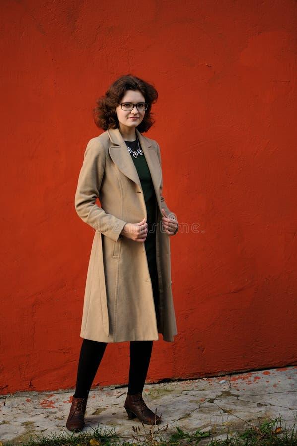 米黄外套的苗条深色的女孩有在褐红的wa的眼镜的 免版税库存照片
