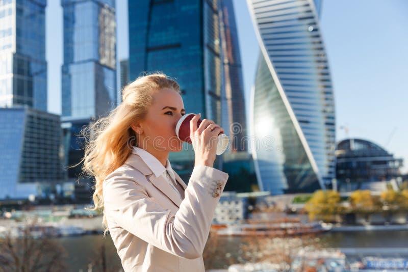 米黄夹克饮用的咖啡的年轻可爱的白肤金发的妇女户外 免版税图库摄影
