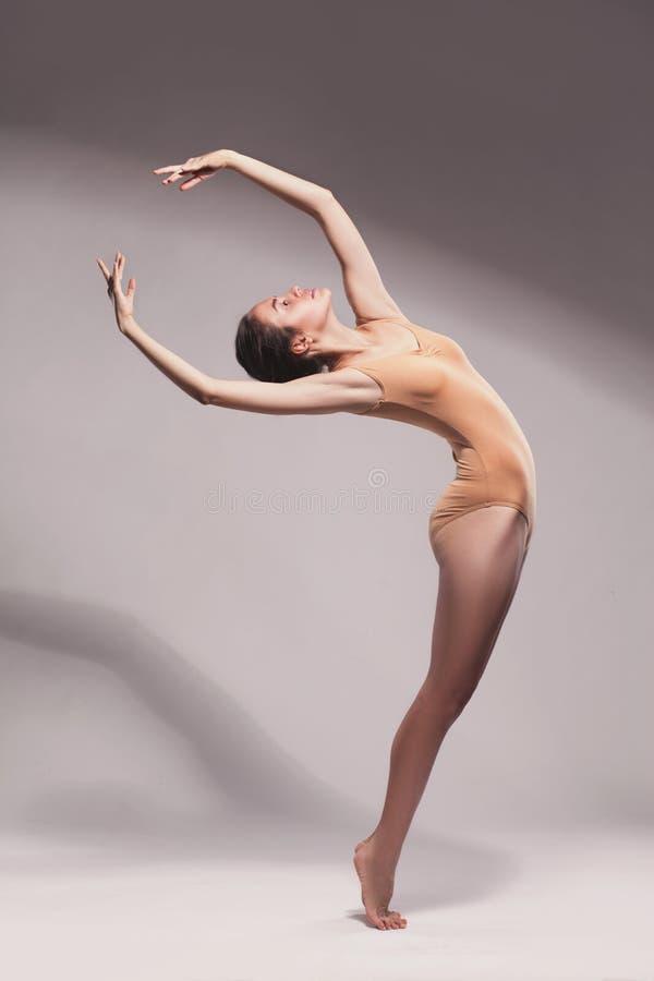 米黄泳装摆在的年轻美丽的舞蹈家 免版税库存照片